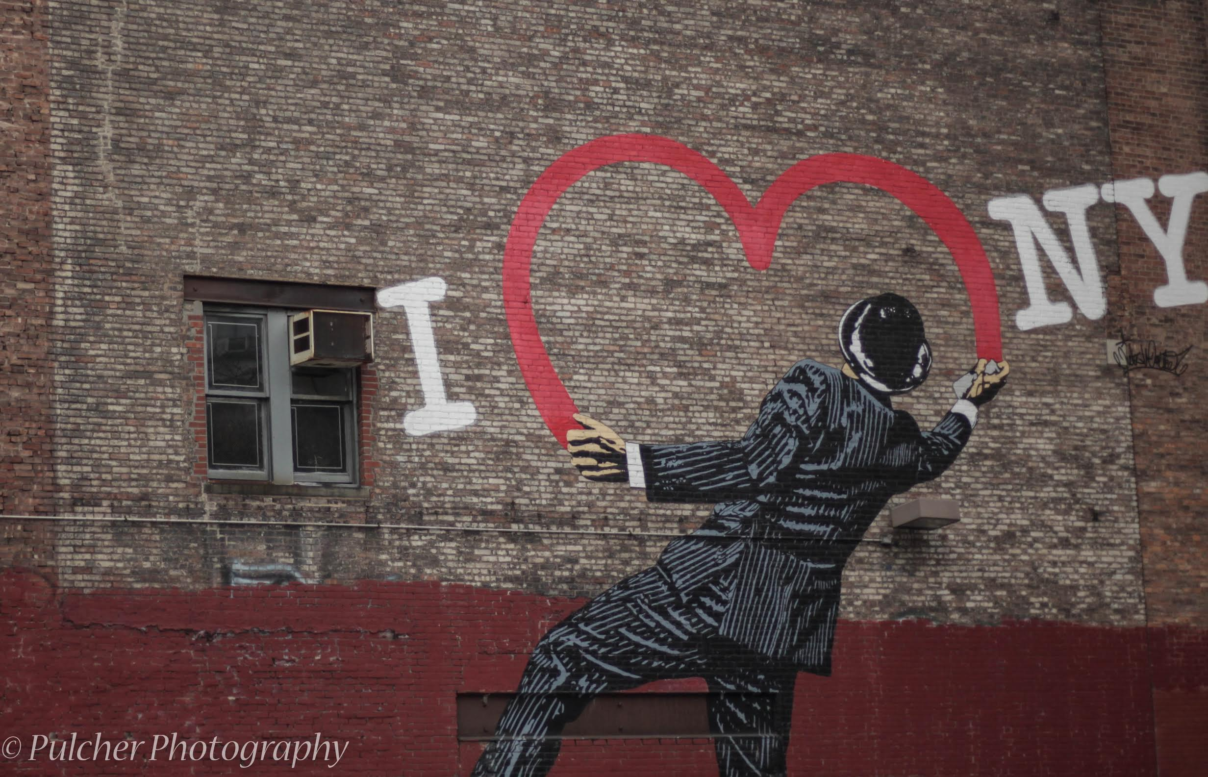 "New York City overflows with art. From Ballet to Broadway, there is something here for everyone. Some of the most interesting art is not found is museums or on stage, but on the street. Street art is filled with passion. Sometimes the messages is as simple as this piece on W 17th St and Avenue of the Americas depicting a man painting ""I <3 NY"" on the side of a building.  50mm f/1.8 iSO 400 1/800."