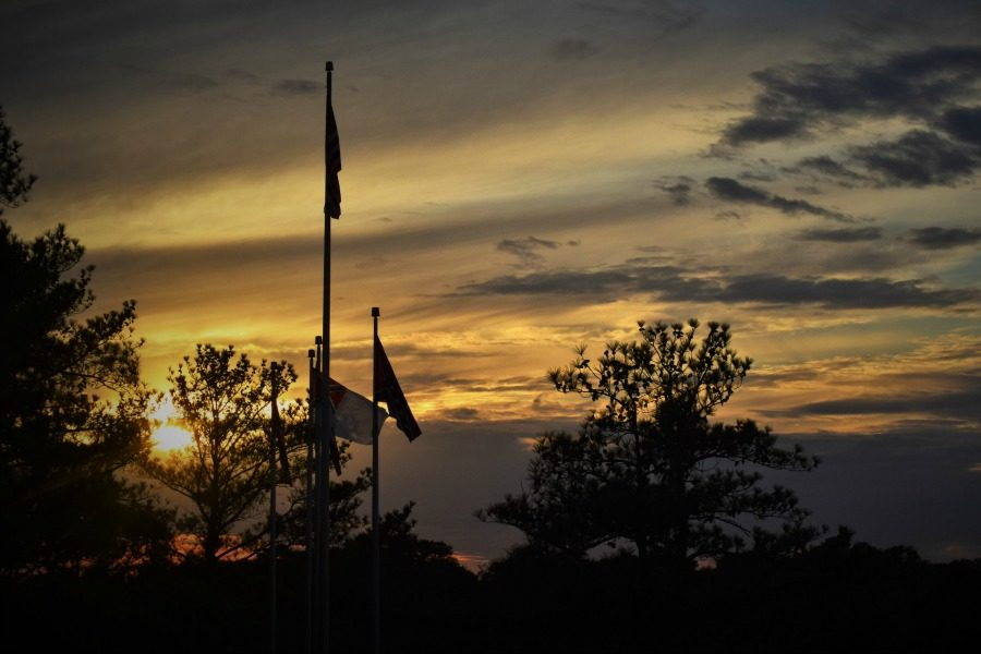 Photo by Christian Hammer. Sunset behind the American flag.