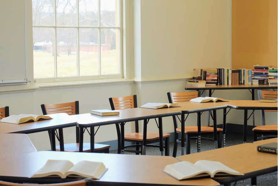 A demo class room set up for the open house. The tables are arranged in a circle to promote discussion and the Socratic method.