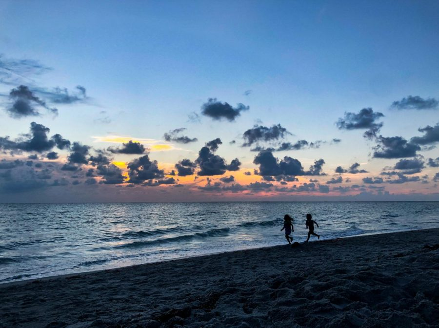 A spectacular sunset while little children chase each other through the waves.